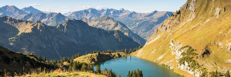 Blick auf einen Bergsee im Allgäu mit Alpenpanorama im Hintergrund
